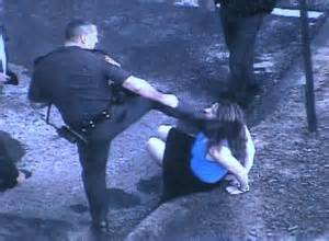 Cop brutally kicks handcuffed woman.